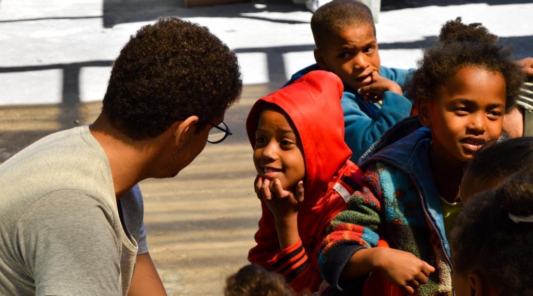 Joven voluntario realizando trabajo social con niños en Sudáfrica.